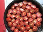 Tagliate i pomodorini a metà e disponeteli su di una teglia oliata da forno antiaderente rotonda.