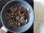 Schiacciate due spicchi di aglio con la buccia e fateli dorare con un filo di olio. Aggiungete i funghi porcini e fate cuocere finchè non saranno cotti e dorati.