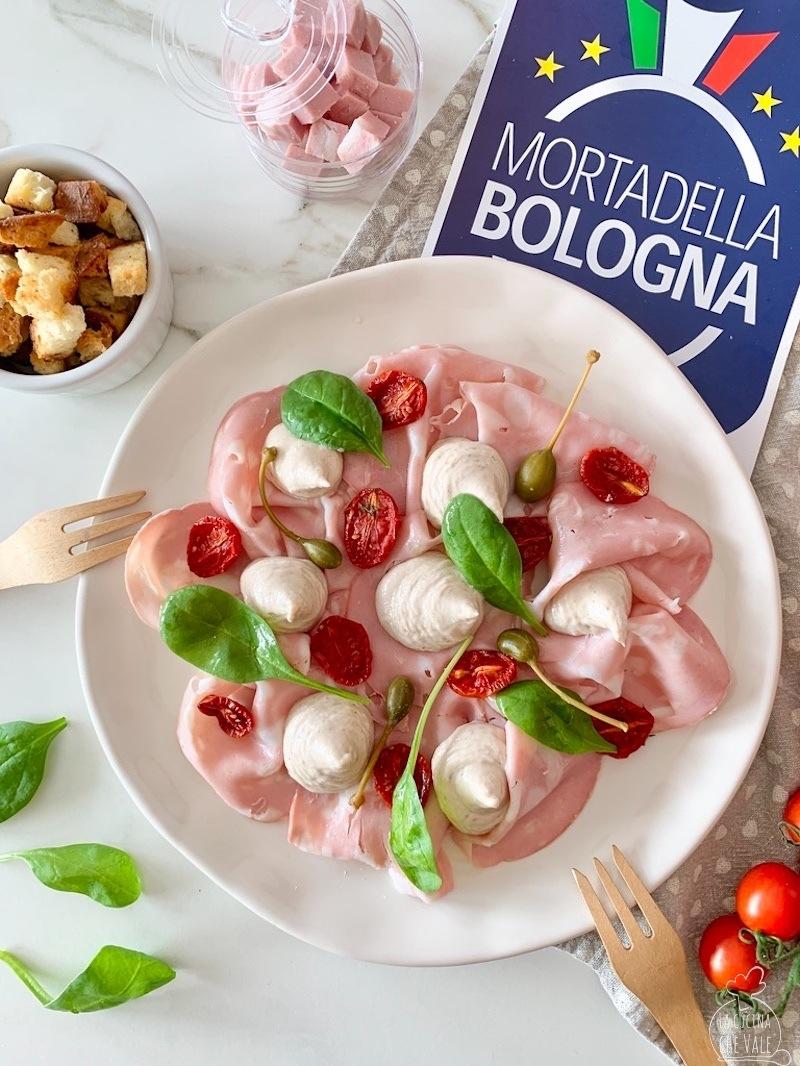 La Mortadella Bologna IGP tonnata è un piatto creativo davvero gustoso dove questo salume viene usata al posto del vitello. E' arricchito con pomodorini confit, salsa tonnata senza uova, spinaci freschi e fiori del cappero.