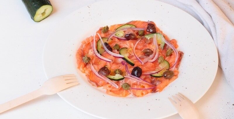 Il sashimi di salmone è un piatto fresco e perfetto per la stagione estiva, bastano pochi ingredienti: il salmone norvegese crudo, le olive, i capperi, i cetrioli e la cipolla rossa.